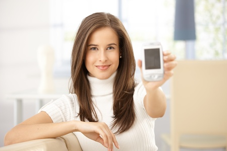 woman smartphone: Portrait of smiling woman holding cellphone up to camera. Stock Photo