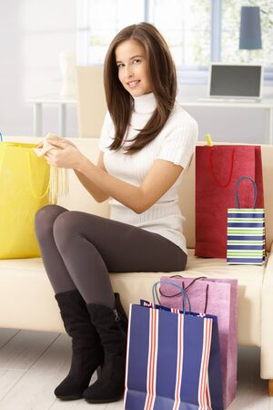 Happy woman after shopping sitting on couch at home with shopping bags, smiling, touching purchase. photo