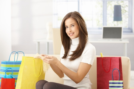 purchased: Smiling woman sitting at home with shopping bags, checking purchased goods, looking at camera.