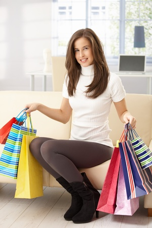 Portrait of happy woman sitting on sofa at home holding shopping bags, smiling. Stock Photo - 8604204