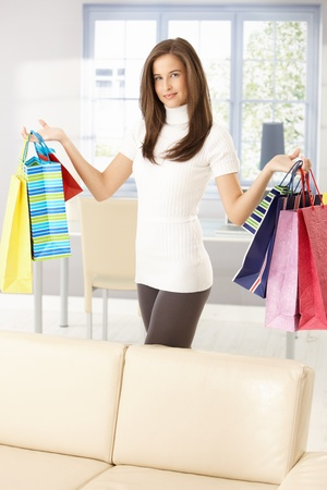 Pretty woman after shopping standing at home, posing holding colorful shopping bags happily. Stock Photo - 8604082