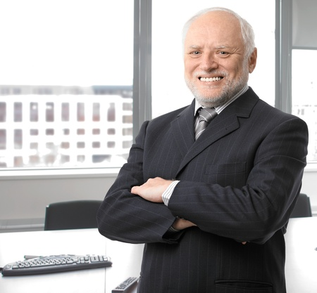 Portrait of happy senior businessman standing in office with arms folded smiling at camera. photo