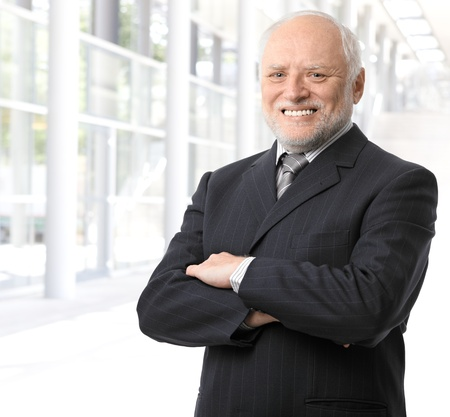 Senior businessman portrait, standing in office lobby with arms crossed, smiling at camera. Stock Photo - 8746969