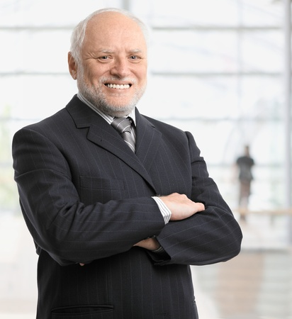 Portrait of successful senior businessman standing in office lobby, smiling. photo