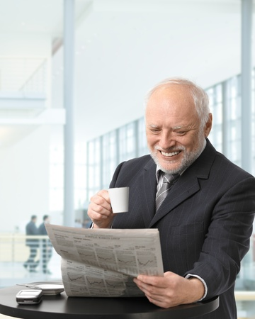Senior businessman on coffee break in office lobby, reading papers, holding coffee cup, smiling. photo