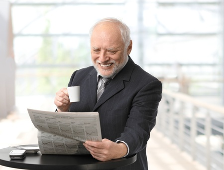 Happy senior businessman reading newspaper in office lobby on coffee break. photo