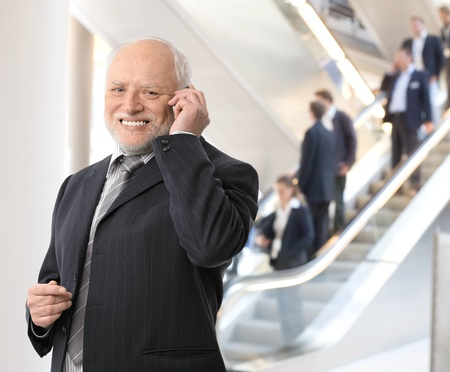 Happy senior businessman standing in office lobby, taking phone call, smiling at camera. photo