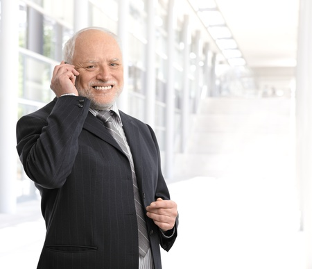 Smiling senior businessman using mobile phone in office lobby. photo
