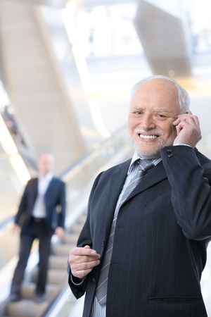 Happy businessman standing in office lobby using cellphone, smiling at camera. photo