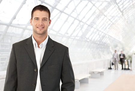Young businessman standing in bright office lobby smiling at camera. Stock Photo - 8746943