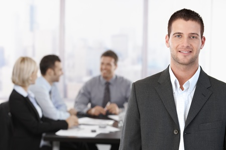 Portrait of young confident businessman in meeting room, with colleagues in background. Stock Photo - 8746961