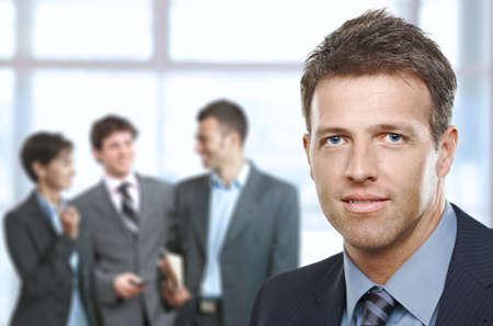 Closeup businessman portrait in office, cheerful colleagues in background. photo