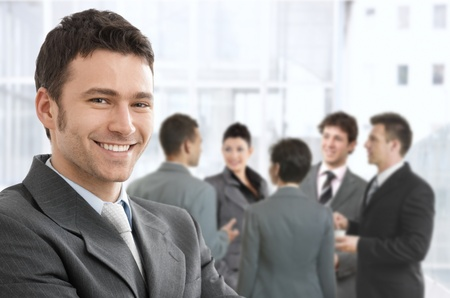 coworker: Smiling confident businessman portrait, group of businesspeople chatting in background. Stock Photo