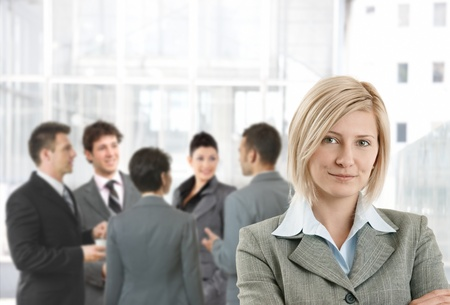 Smiling businesswoman in office lobby, colleagues talking in background. Stock Photo - 8746956