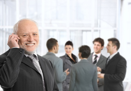 Senior businessman talking on mobile phone in office lobby, smiling, businesspeople chatting in background. photo