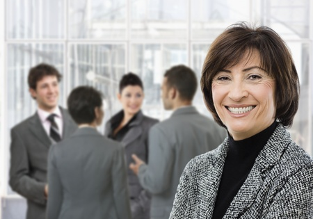 Senior businesswoman smiling, looking at camera, businesspeople in conversation in lobby. photo