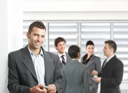 Confident businessman standing with mobile phone in hand in meeting room, colleagues talking. photo