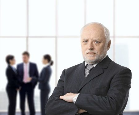 folded arms: Portrait of serious senior businessman standing with arms folded in office lobby, colleagues in background. Stock Photo