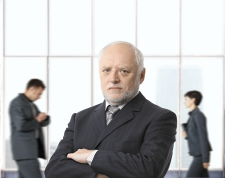 Severe senior businessman with arms crossed in office lobby, looking at camera. Stock Photo - 8746944