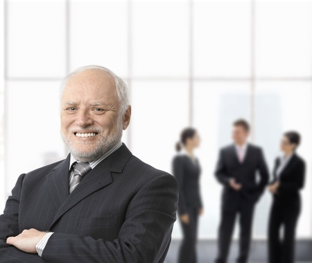 Portrait of smiling senior businessman standing with arms folded, businesspeople in background. photo