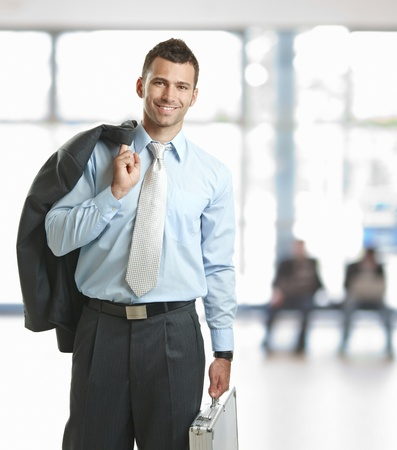 Smiling businessman standing in lobby with suitcase, leaving office. photo