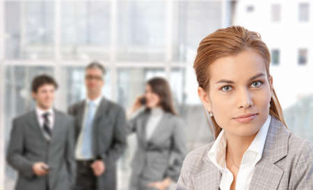Closeup portrait of young attractive businesswoman, businesspeople in background of lobby. photo