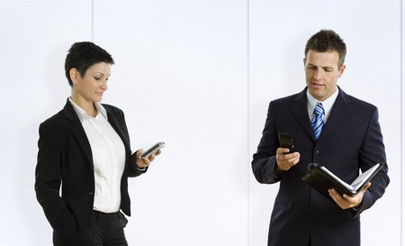 sms text: Busy businesspeople using mobile phone and personal organizer.