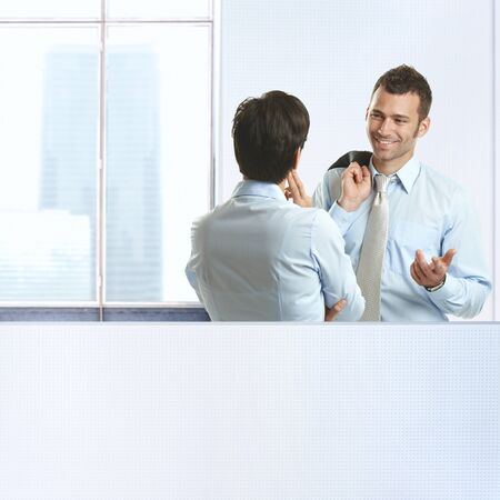 Two coworkers standing chatting in business office, smiling. photo