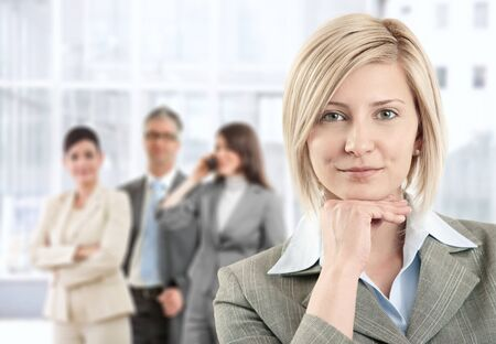 Portrait of smiling businesswoman posing at camera with team in background of office lobby. photo