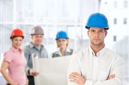 severity: Architect in hardhat standing with team holding plan in office.