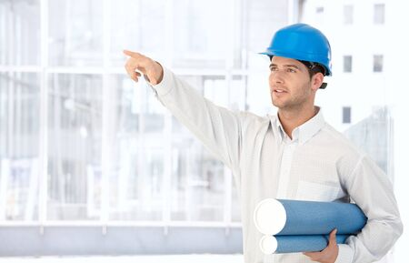 Architect wearing hardhat holding work plan standing in office, pointing. Stock Photo - 8746941