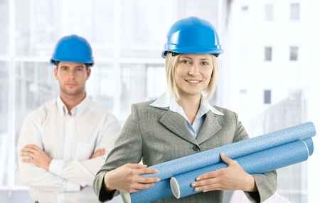 Creative designers standing in office smiling in protective wear in office, holding work plan. Stock Photo - 8746964