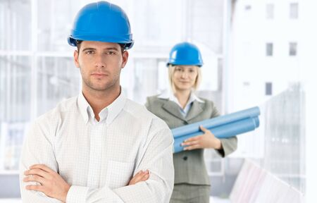 Portrait of architect standing in office in hardhat, looking at camera, coworker with work plan in background, photo