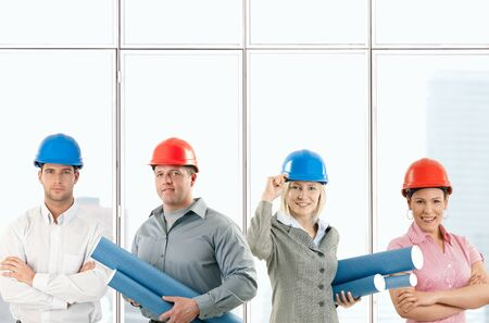 Portrait of happy architect team standing in office, wearing protective hardhat, holding work plan. photo