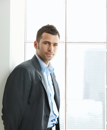 Portrait of businessman standing at office window, looking at camera, smiling. Stock Photo - 8746976
