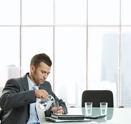 water jug: Thirsty businessman sitting at meeting table pouring water from jug into glass to drink in meeting break. Stock Photo