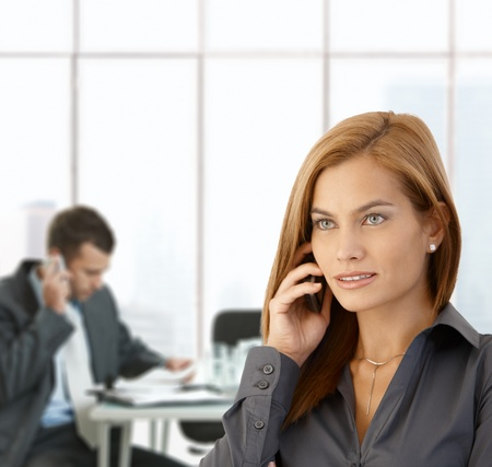 Businesswoman busy taking phone call in office, coworker working at meeting table. Stock Photo - 8746950