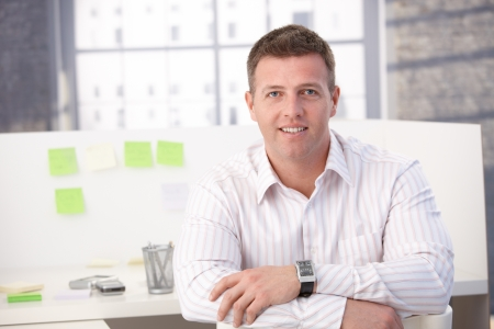 only 1 person: Male casual office worker smiling in office, sitting.