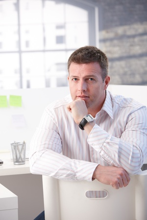 Mature man sitting on chair conversely in office, thinking. photo