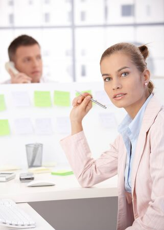 Attractive young girl working in modular office, man in background talking on phone. photo