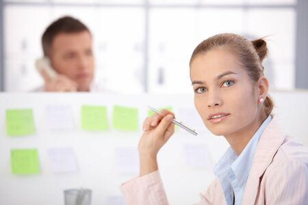 Pretty young female office worker sitting at desk in office, man in background. photo