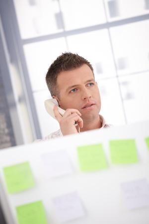 tabique: Trabajador de la Oficina de varones j�venes hablando por tel�fono detr�s de partici�n.