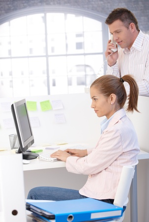 Casual office workers busy in office, using computer and phone, working. Stock Photo - 8747039