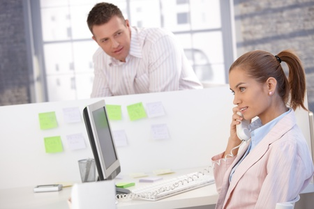 Pretty girl working in office, talking on phone, colleague looking at her. photo