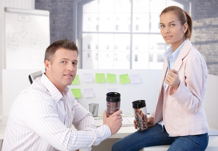 women holding cup: Colleagues during coffee break in office, chatting drinking coffee.