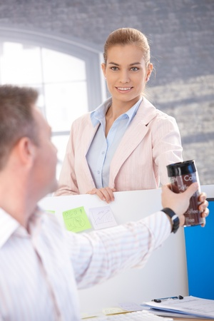 Attractive young woman passing coffee to male colleague, smiling. Stock Photo - 8747070