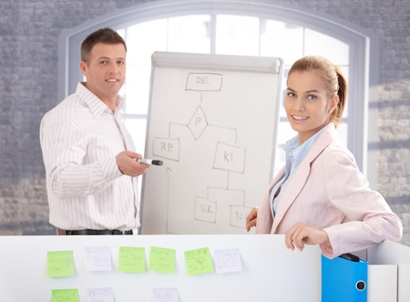 Young people working together in office, using whiteboard, smiling. Stock Photo - 8747048
