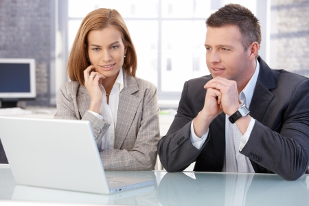 Attractive young businesspeople working together in office, using laptop. Stock Photo - 8747147