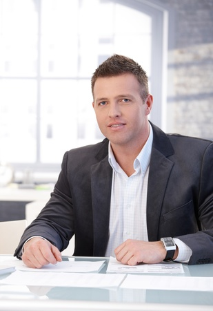 Handsome businessman working at desk in bright office. photo