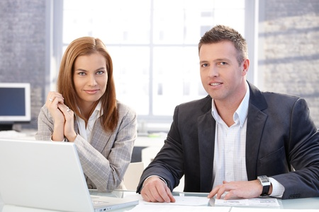 Attractive businesspeople working on laptop in bright office, smiling. photo